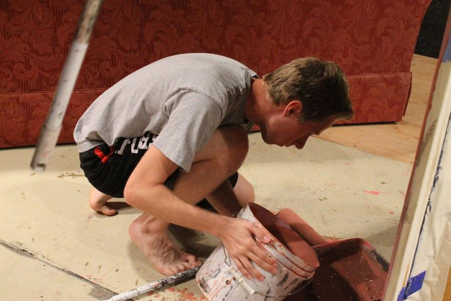 Kodi Reed, 10, poring paint into a paint pan so he can put a light red gloss over the Steel Magnolias set in Tech Theater on April 15th.