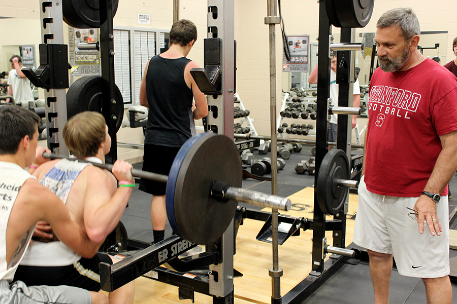 """Mike Dumpert, strength teacher, encourages a student in the strength class. Dumpert has been teaching for 30 years. """"I don't care how much the boys lift, as long as they are putting 110% in each class,"""" Dumpert said."""