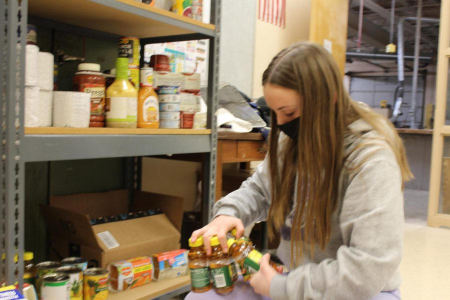 "Hayley Hines, freshman, puts apple juice on the food pantry shelves on Mar. 4. Hines loves the food pantry because it helps people in need. ""It"